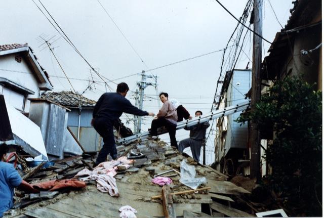 1995年1月17日午前7時40分頃、神戸市灘区にて撮影。近隣住民が2Fに閉じ込められた老人を救出している様子。